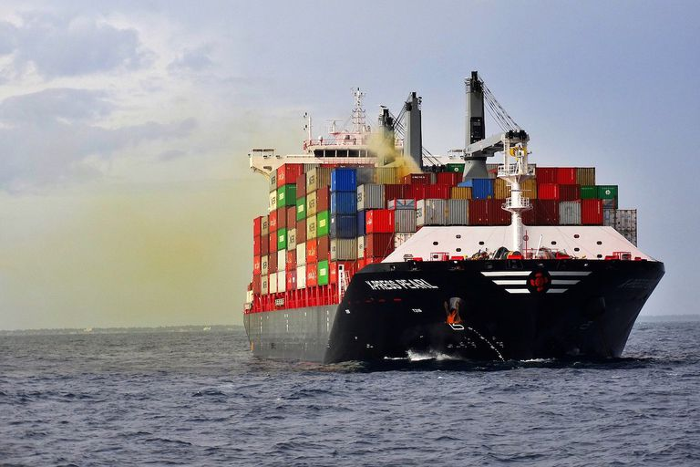 Cargo ship at sea with brownish fumes coming from a container amidships