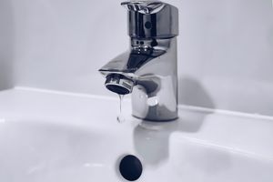 Drip of water coming from sink's water faucet
