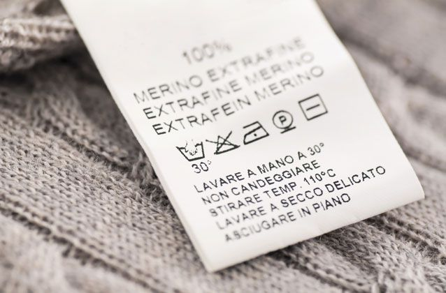 A laundry care tag on a merino sweater