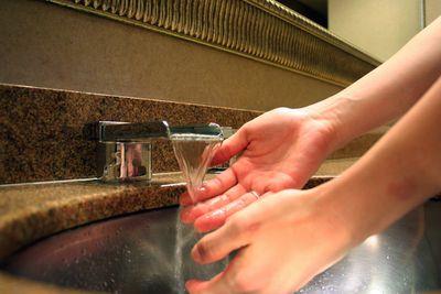 Human hands under running water in a sink