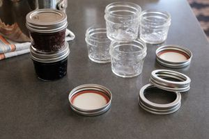 two jelly jars next to stack of empty jelly jars and canning lids for reuse