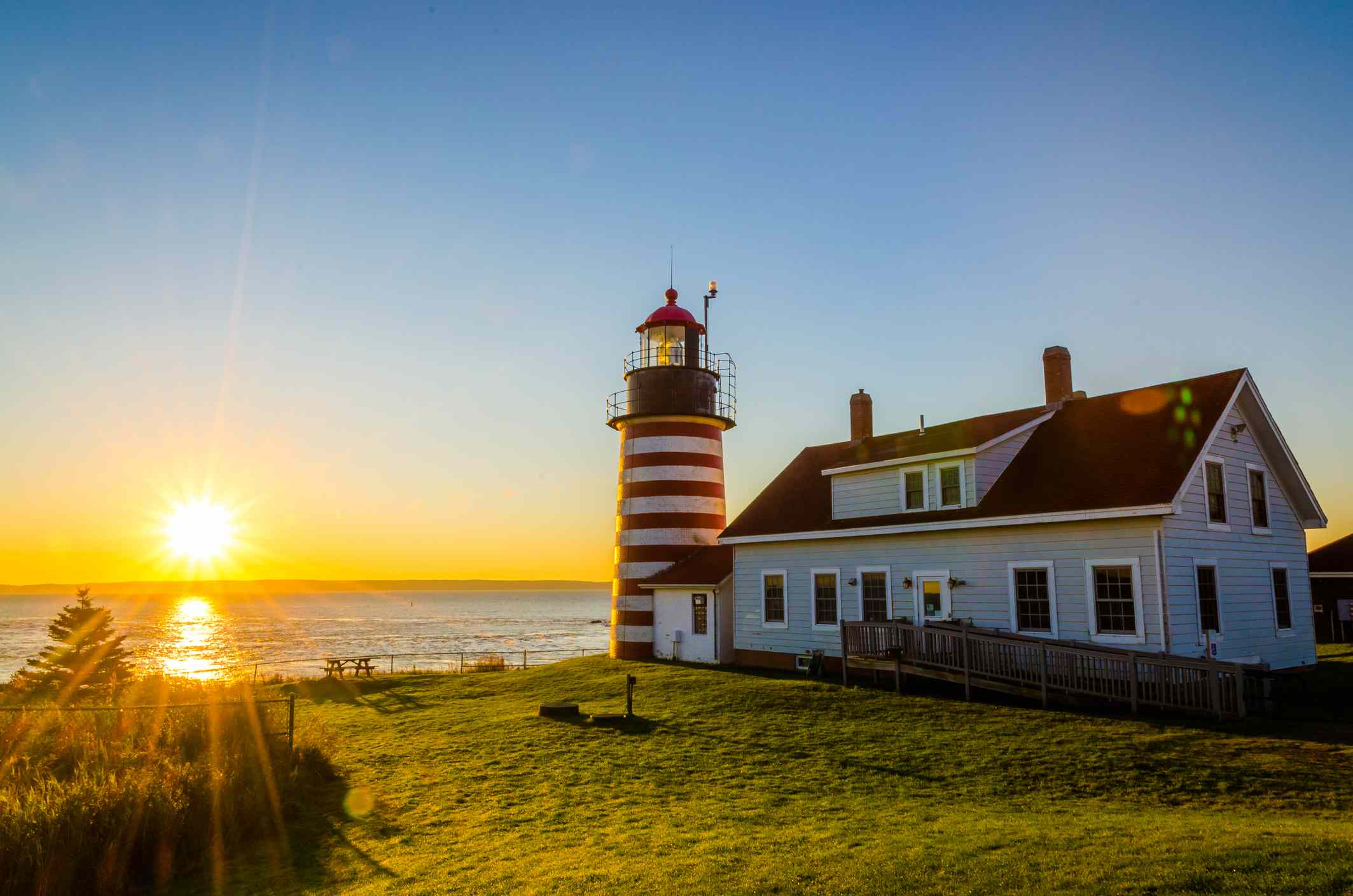 West Quoddy Head Lighthouse with sun rising over the ocean