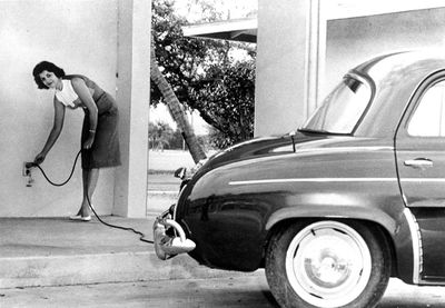 View of a woman charging the 'Henney Kilowatt', an electric automobile.