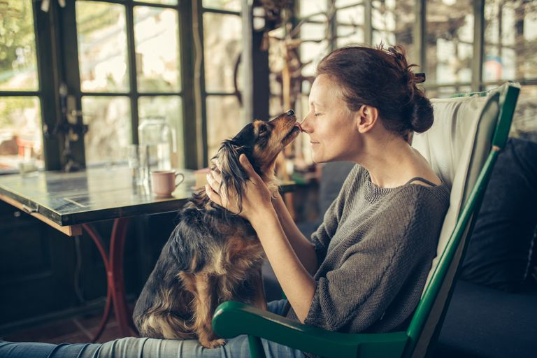 woman at home with dog in arms