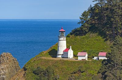 Heceta Head Lighthouse on the edge of a green cliff overlooking the bright blue Pacific Ocean with a light blue sky in the distance