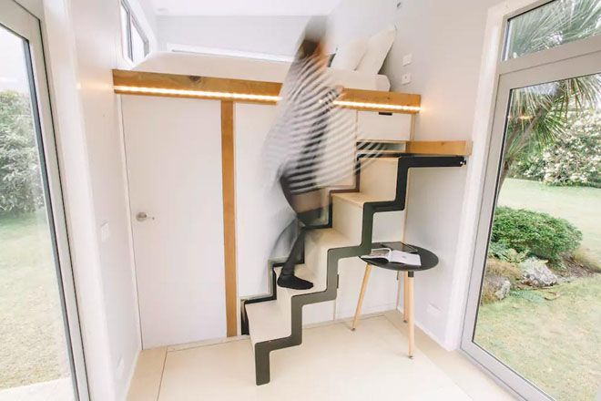 Hidden staircase pulled out with blurred image of someone walking up it