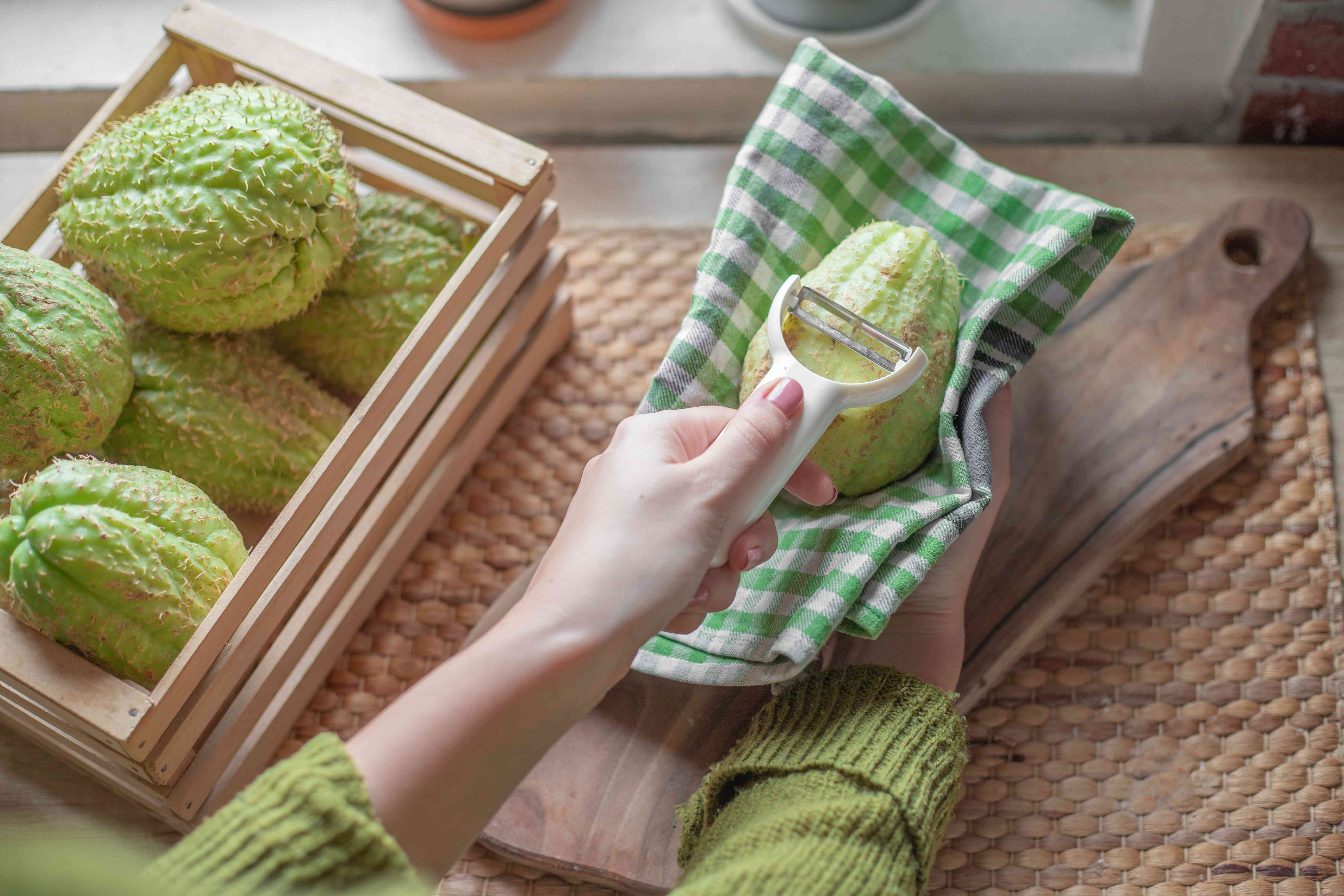 hand in green sweater peels a chayote