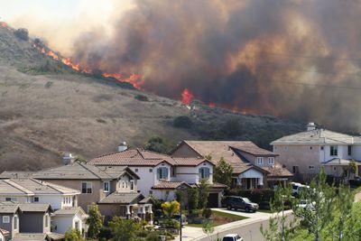 Wildfire burns near a neighborhood on a sunny day