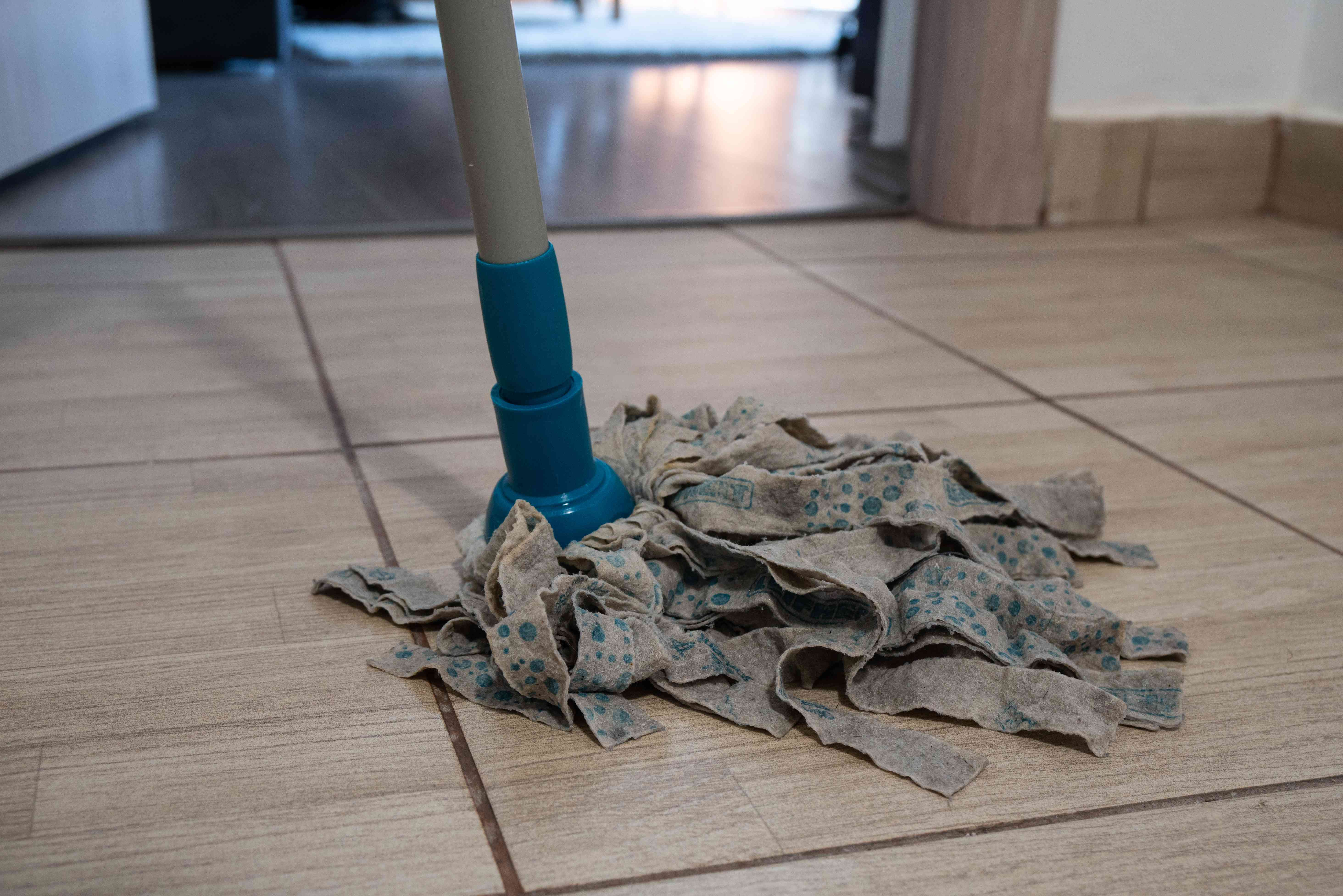 floor shot of blue and gray fabric mop being used on vinyl floor