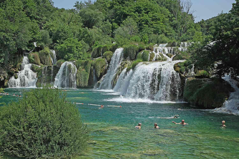 Swimmers enjoy the blueish-green pool at the base of Skradinski Buk cascading falls