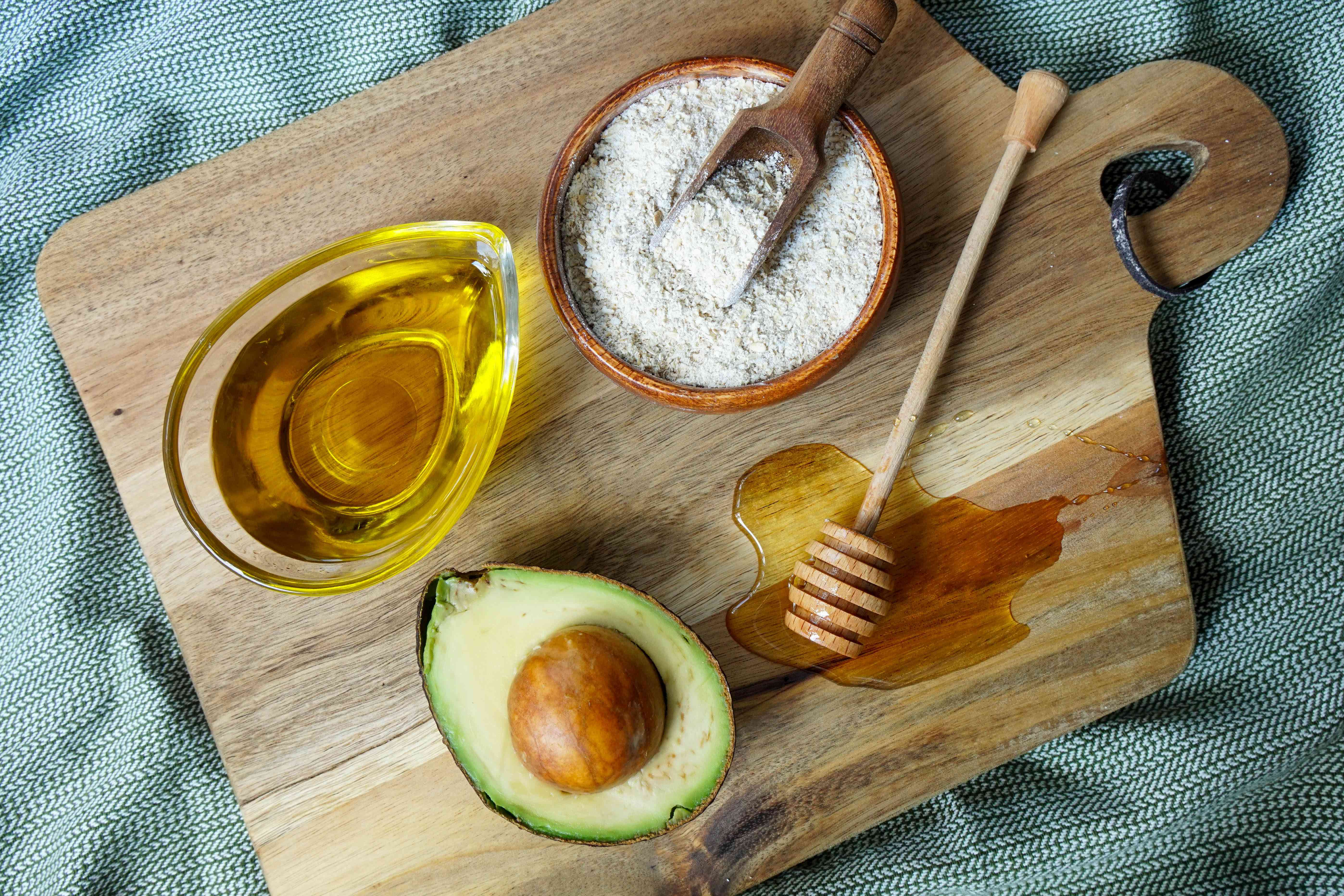 ingredients for avocado honey olive oil mask on cutting board