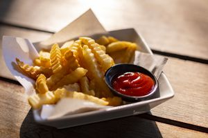 Tasty French Fries On Wooden Table