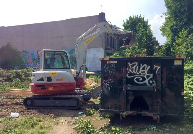 A small bulldozer places the remains of a city garden into a dumpster