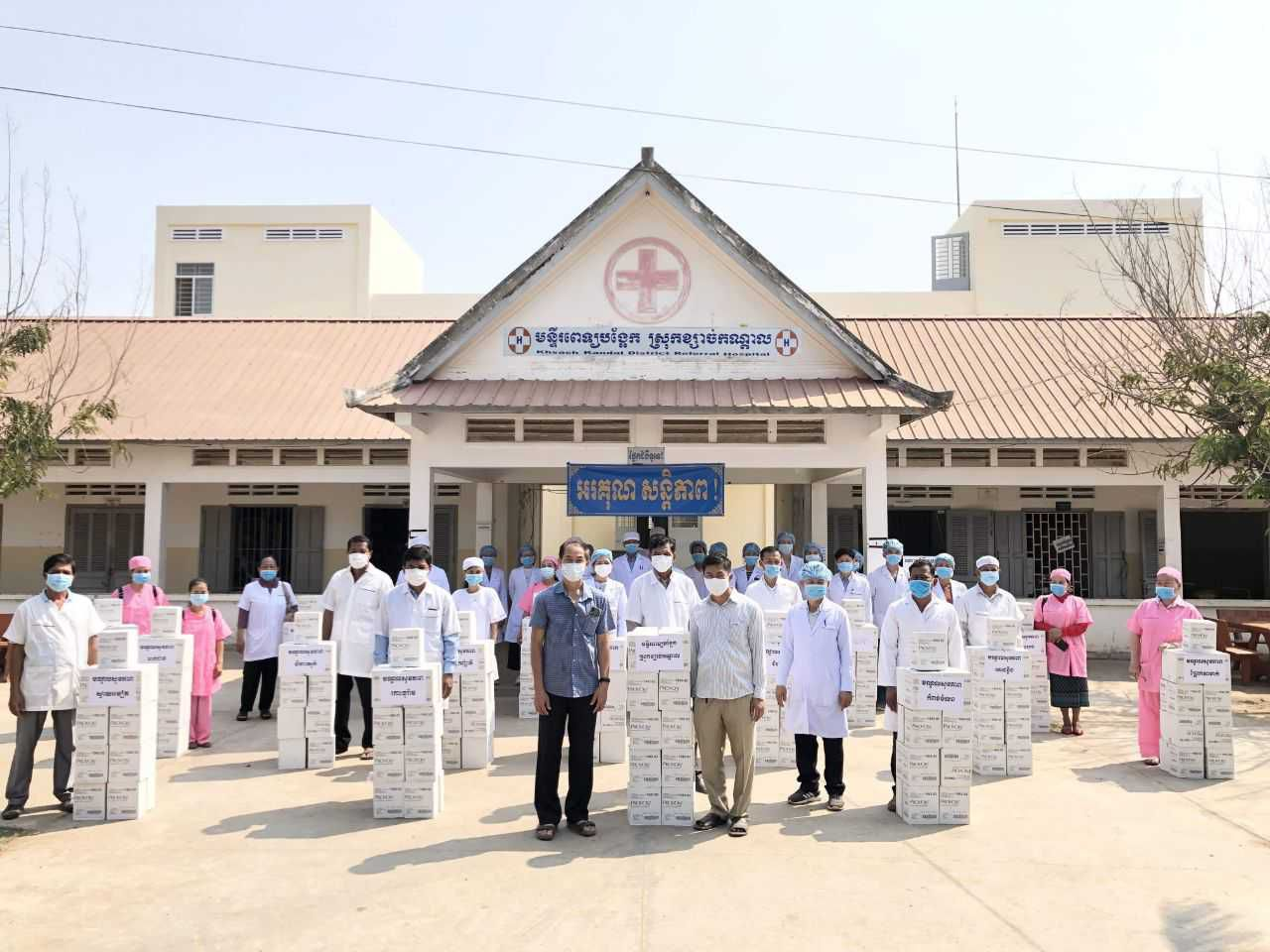 Healthcare workers wear masks outside a facility with donated soap in Cambodia during pandemic
