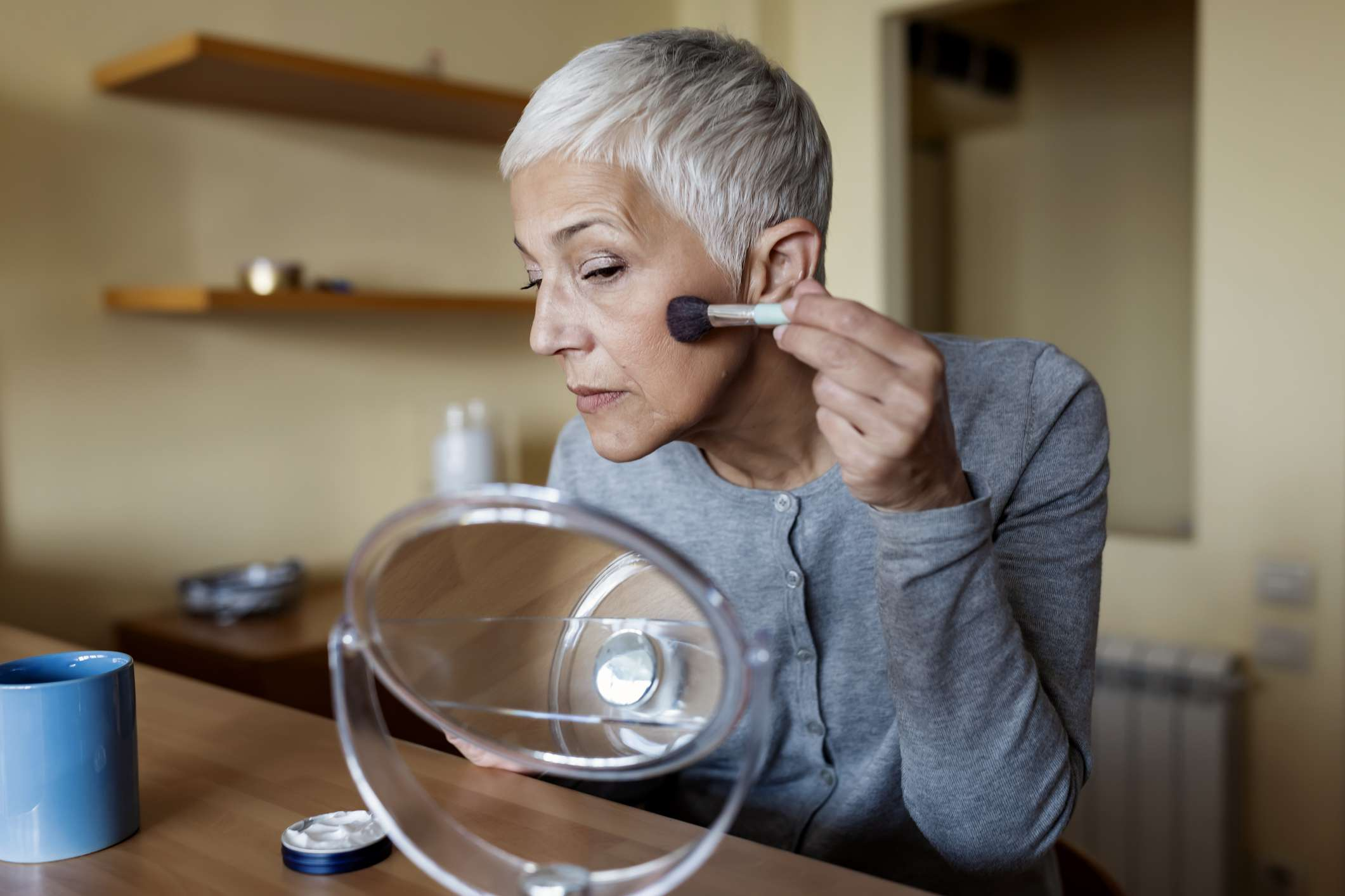 A mature woman with short silver hair applies blush to her face.