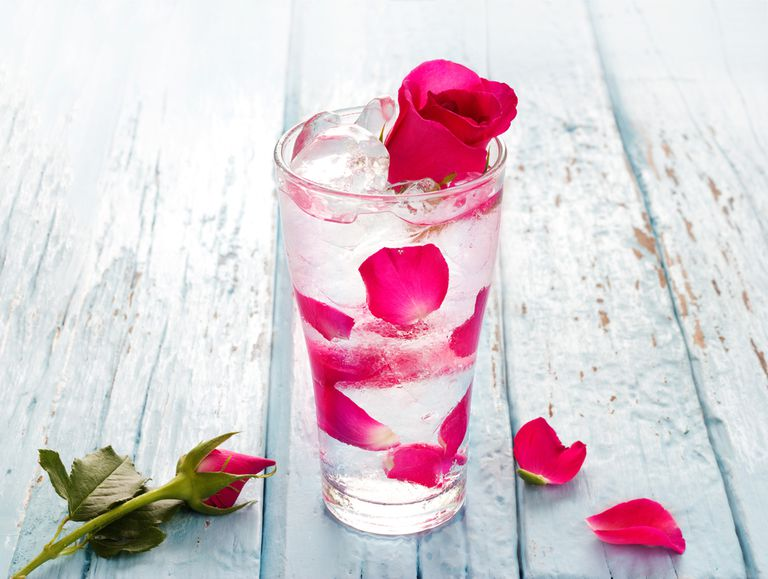 Glass of water with rose petals in it and a rose on the table