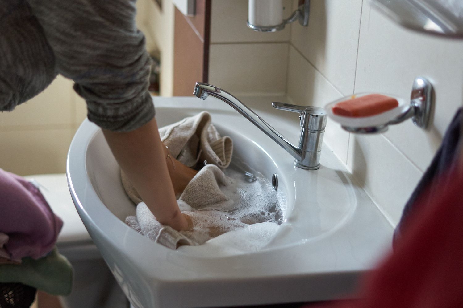 person gently washes sweater in small bathroom sink with soap and water