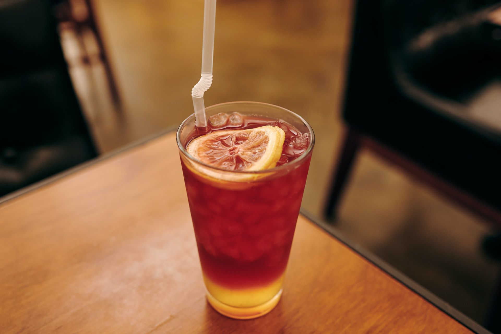 Glass of rhubarb iced tea topped with a lemon