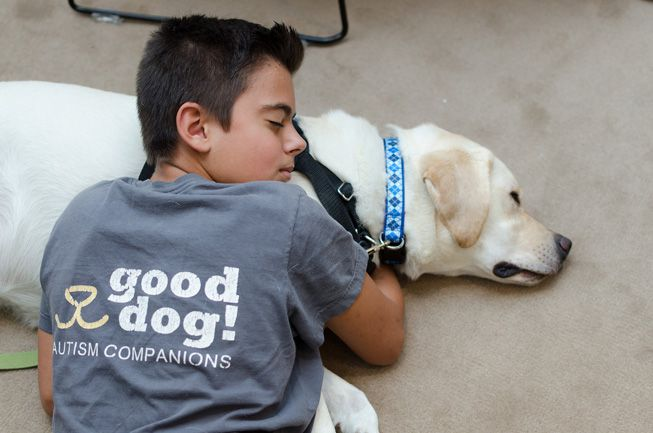 An boy with autism cuddles with a therapy dog