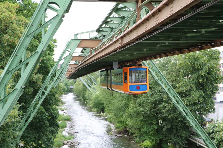 Train car hanging upside down over waterway in Wuppertal, Germany