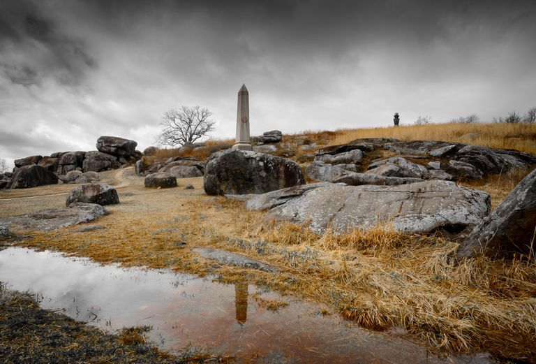 Overcast sky over a rocky landscape with a single tree and sparse stone monuments