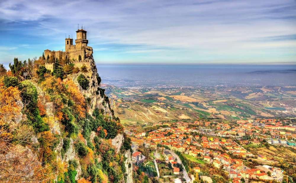 A castle sits atop a cliff looking over a vast valley town below in San Marino