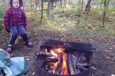 small child sitting in front of a fire in a kettle in the woods