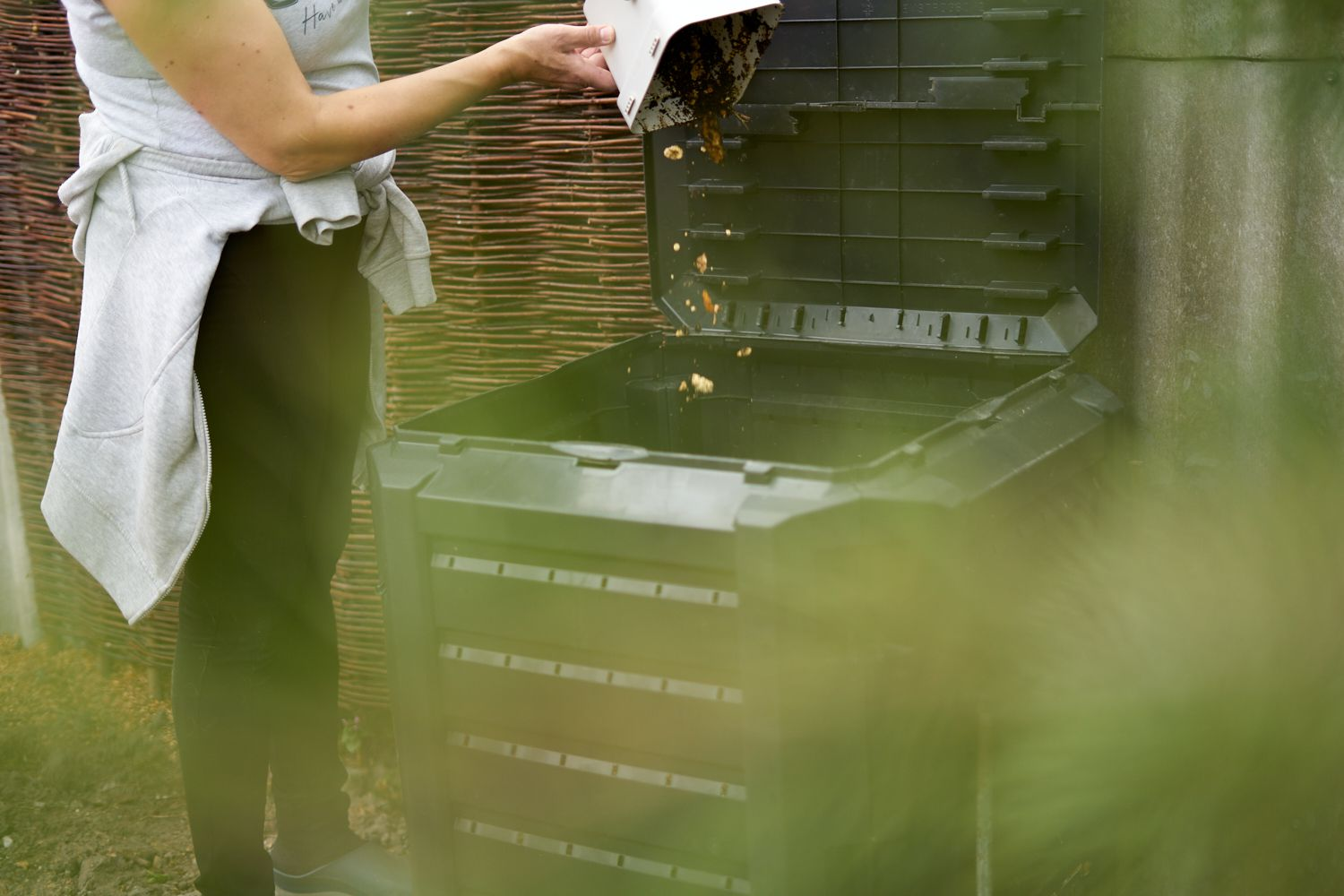 person dumps old food waste from white bin into large black composter