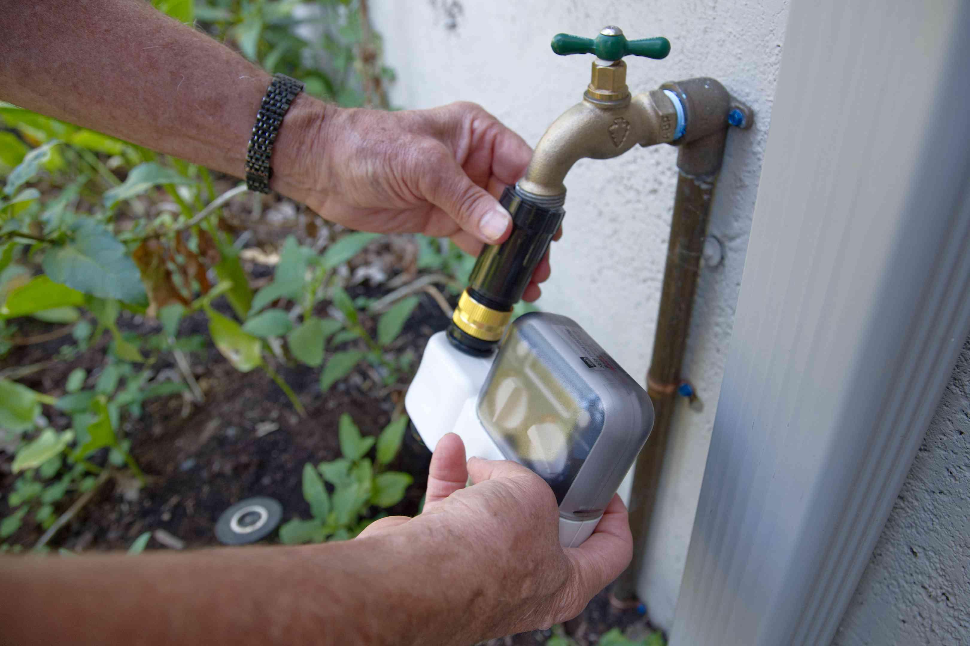 hands attach a timer and pressure regulator to the main hose line