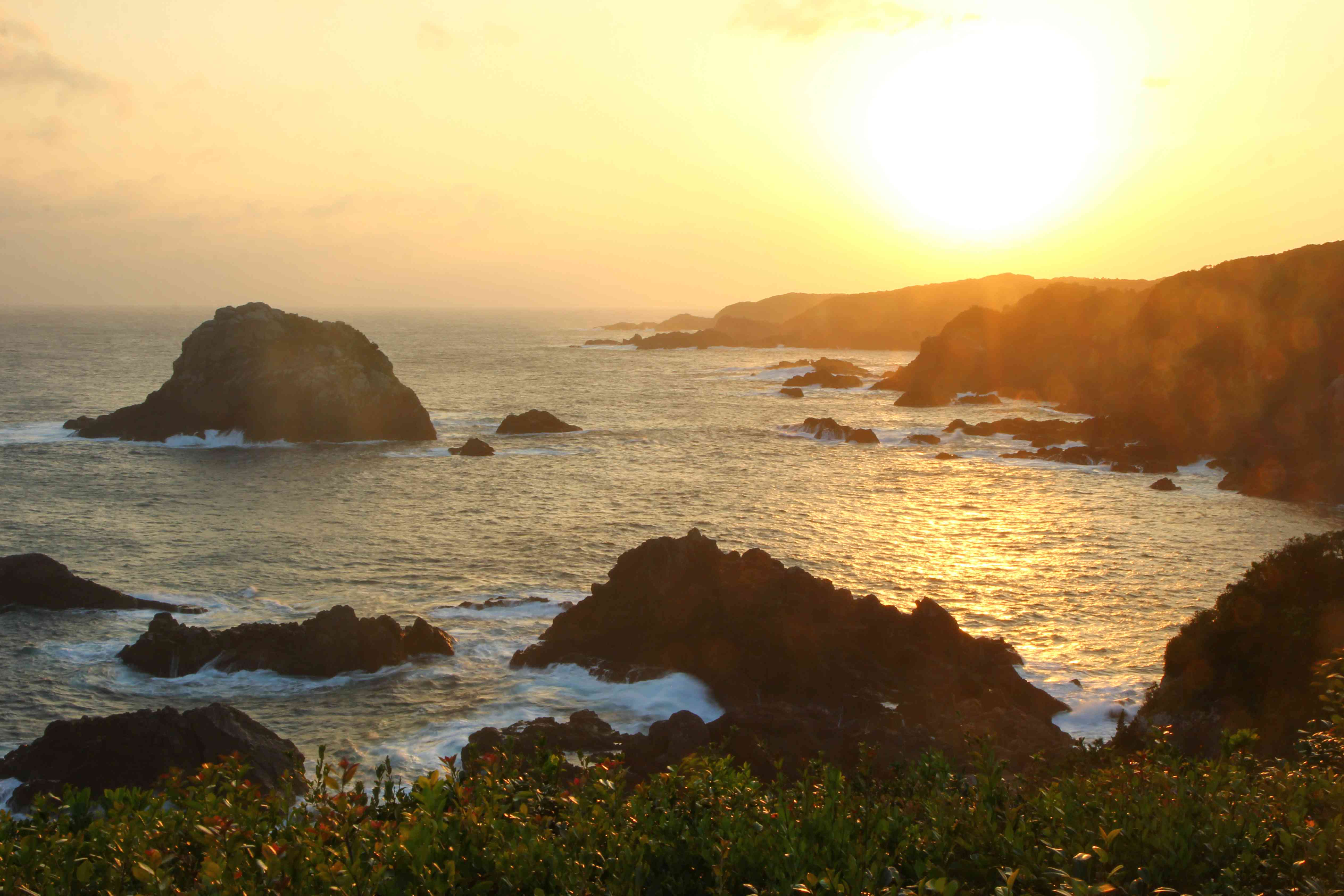 rocky ocean coast with jutting exposed rock formations at sunset