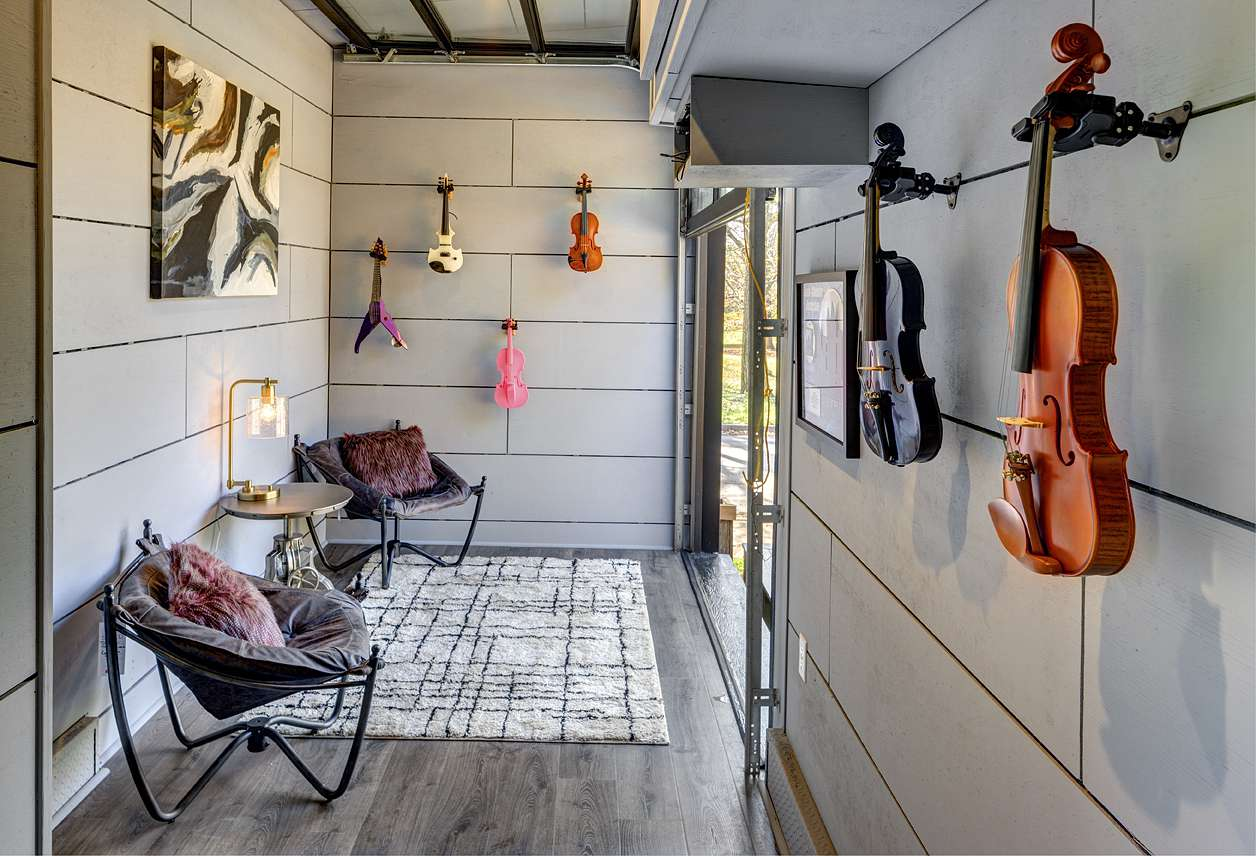 Practice studio with various violins hanging on the walls