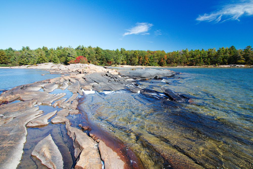 Large shale rocks above the waterline surrounded on two sides by water with a large stand of green trees in the distance under a blue sky at Killbear Provincial Park