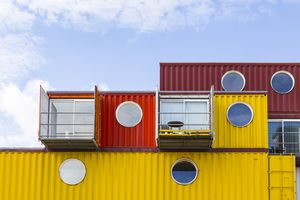 Red and yellow container houses stacked on top of one another.
