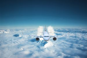 Passenger airplane flying above the clouds