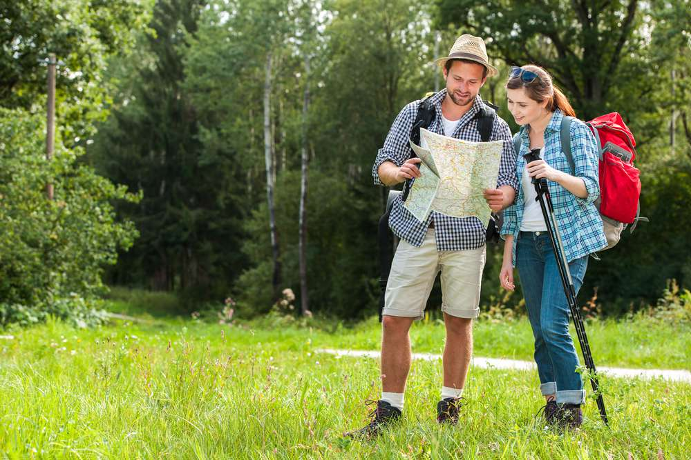 couple looking at map in the woods