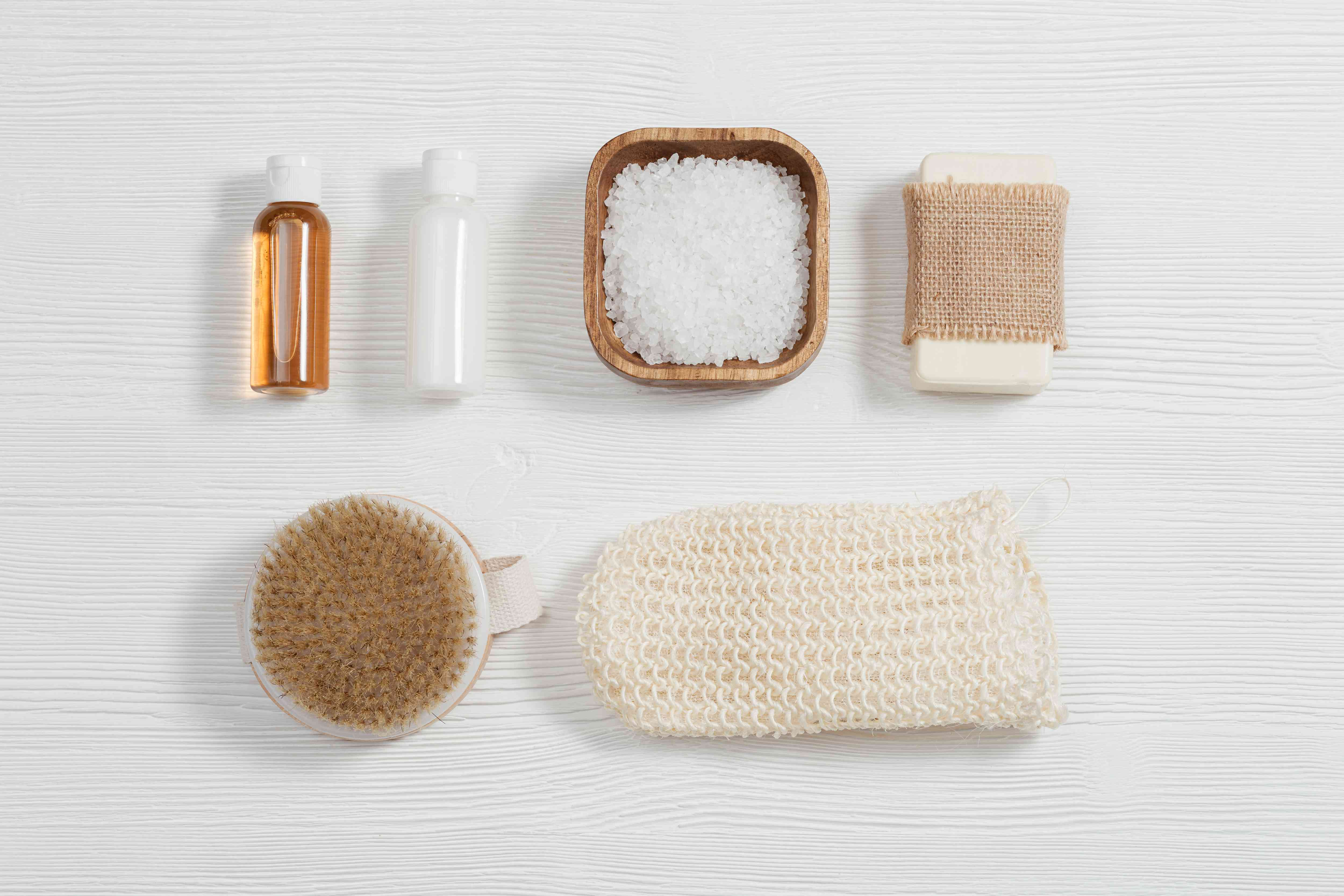 Spa setting for body care and beauty treatment. Bottles with gel and shampoo, soap, sea salt, washcloth for bath.