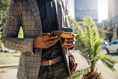 Midsection Of Businessman Text Messaging And Holding A Cup Of Coffee