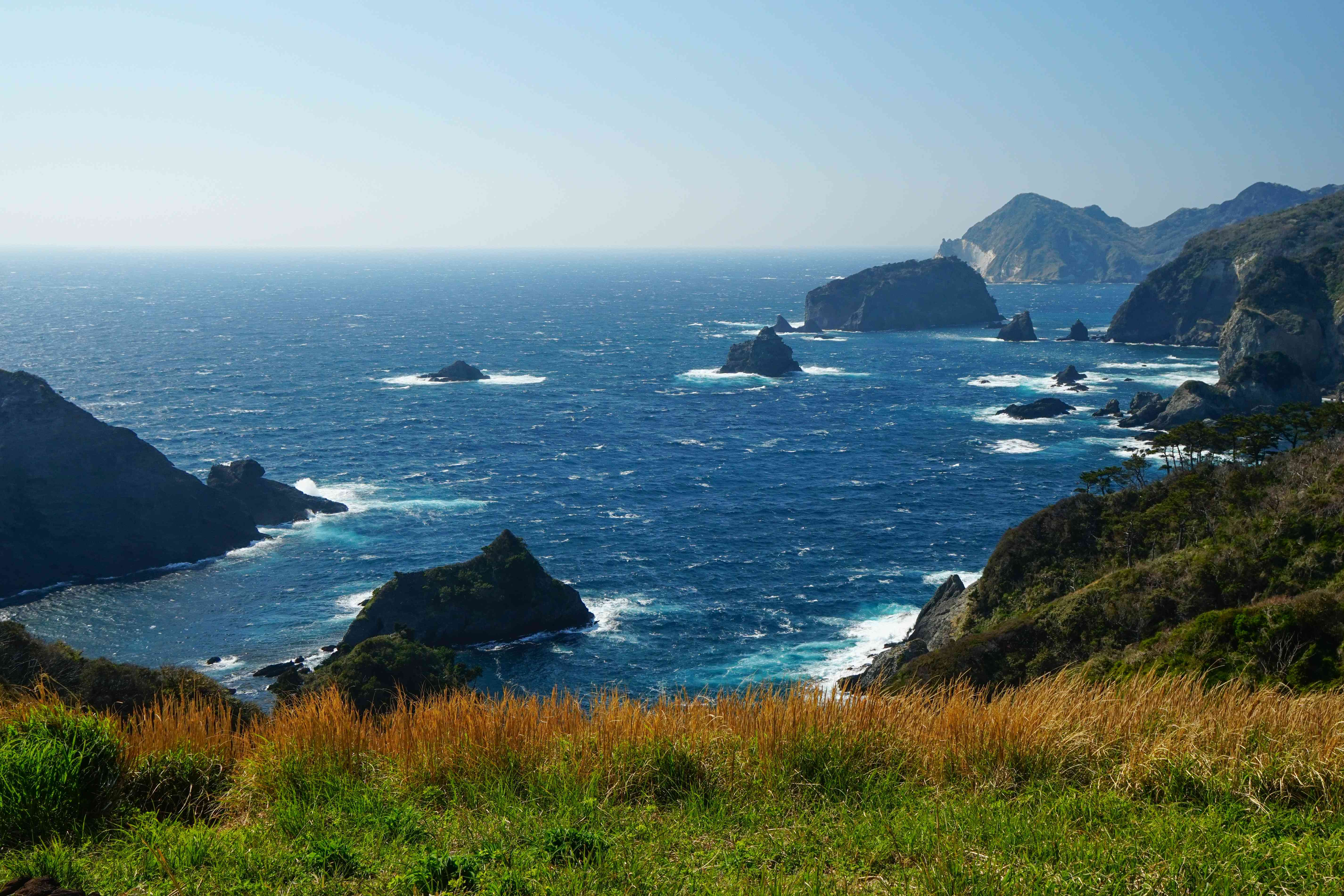 coastline with green grass and rocky formations in background with deep blue ocean water