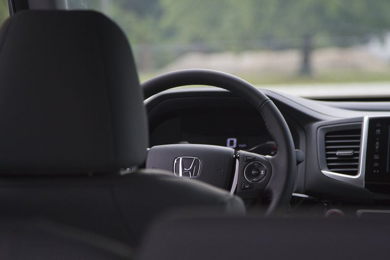 A Honda steering wheel and front seat without passenger.