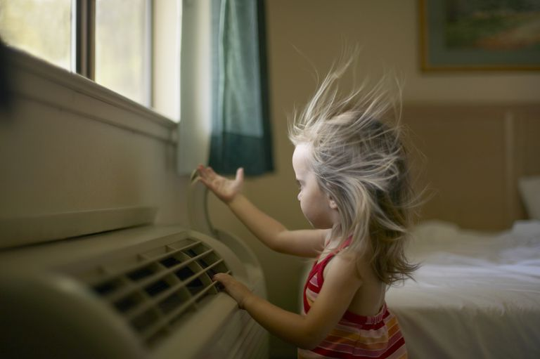 Toddler feeling air coming from room air conditioner