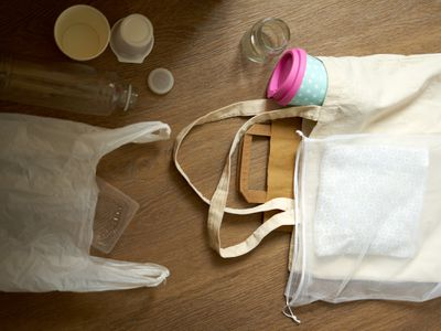 flat lay shot of plastic bag, reusable bags, reusable coffee cups, and plastic items