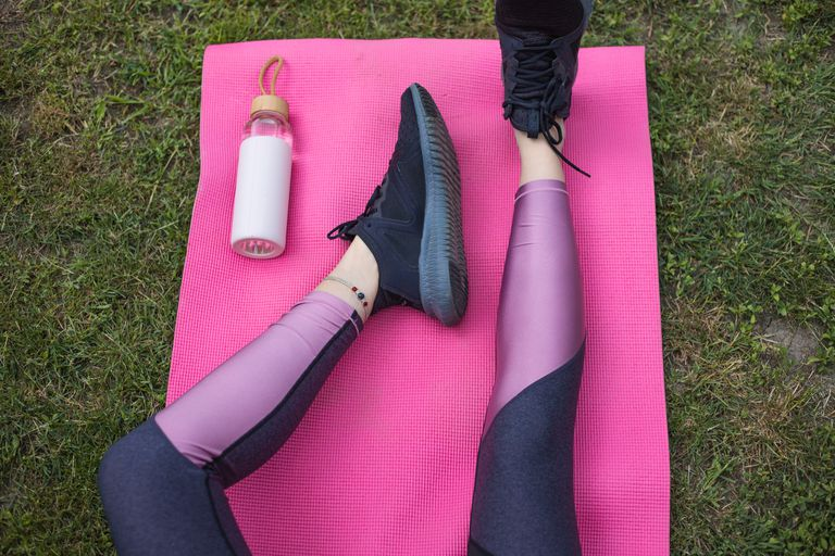 person wears color-blocked leggings sitting on pink yoga mat outside on grass