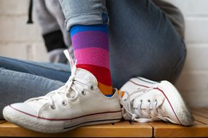 Person sitting on a bench wearing white converse and colorful striped socks