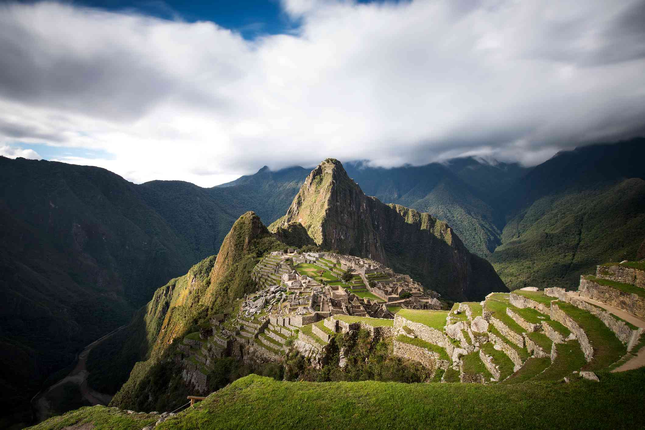 View of the mountains and ruins of Machu Picchu covered in lush green plants under thick clouds with a bit of blue sky