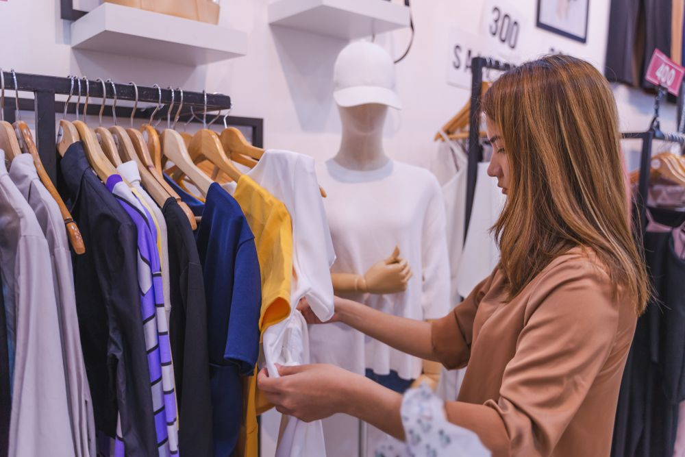 young Asian woman choosing clothes at store shop