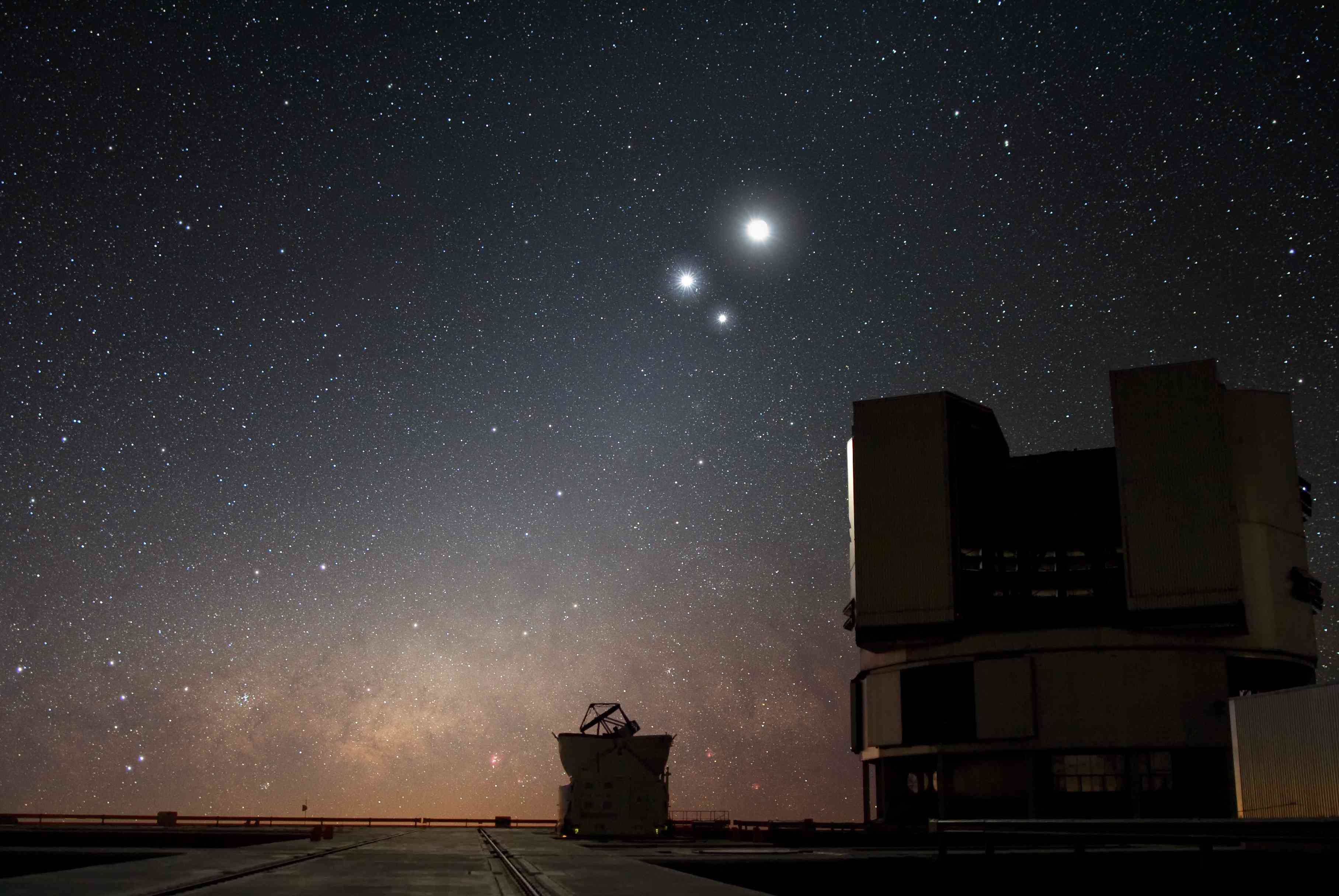 a large telescope with the moon, Jupiter and Venus in the background