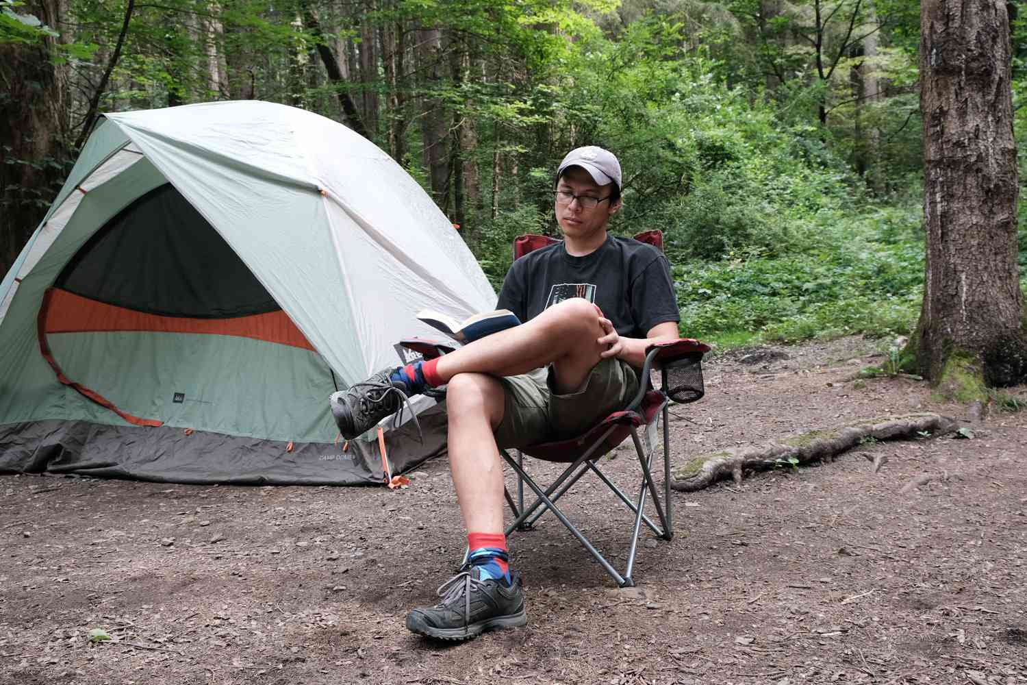 guy reads book in lawn chair next to tent while camping outside
