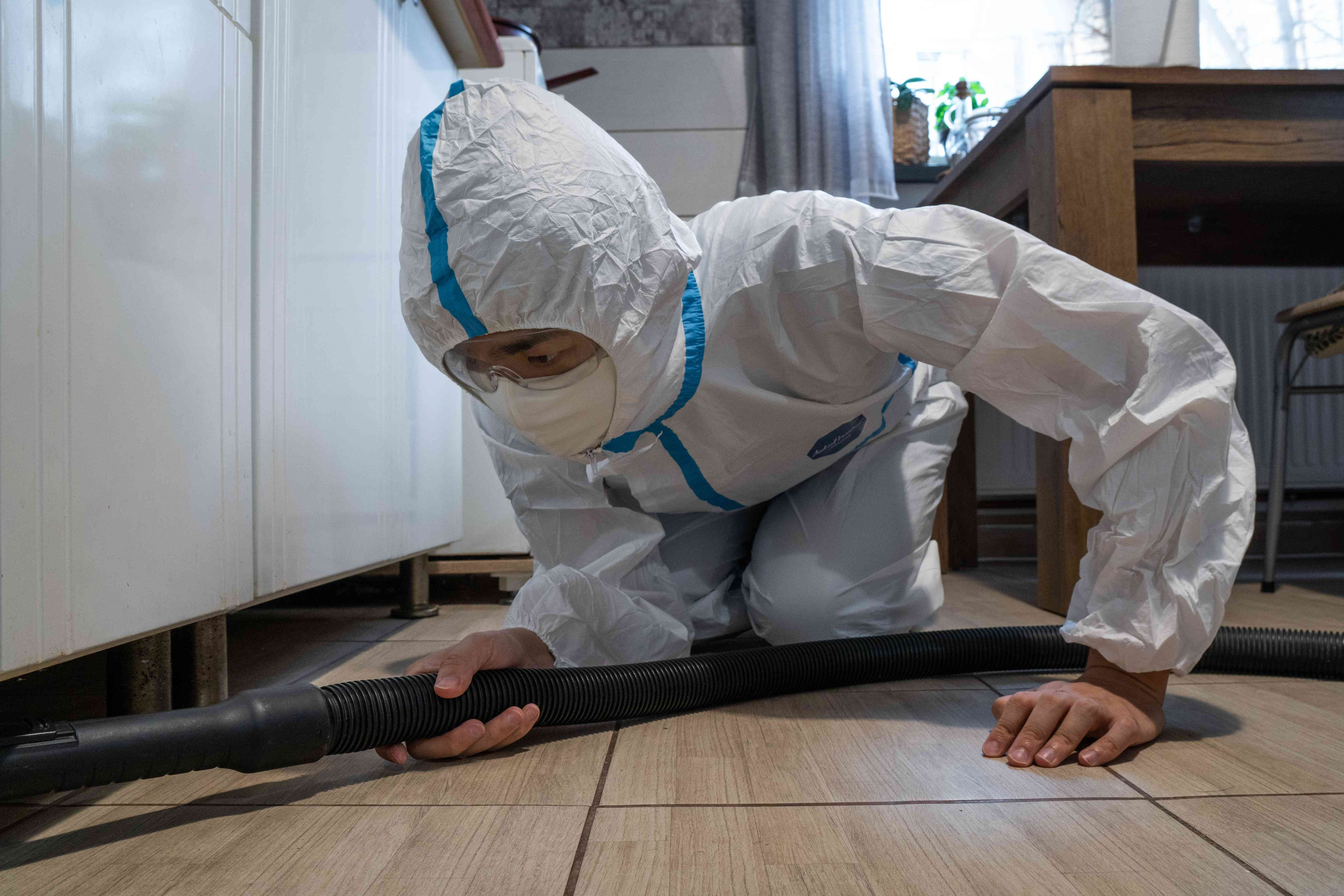 bug expert in hazmat suit and mask crouches on ground with large hose under cabinets