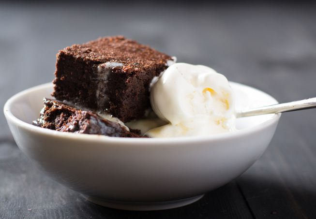Warm brownies in a white bowl with melting vanilla ice cream
