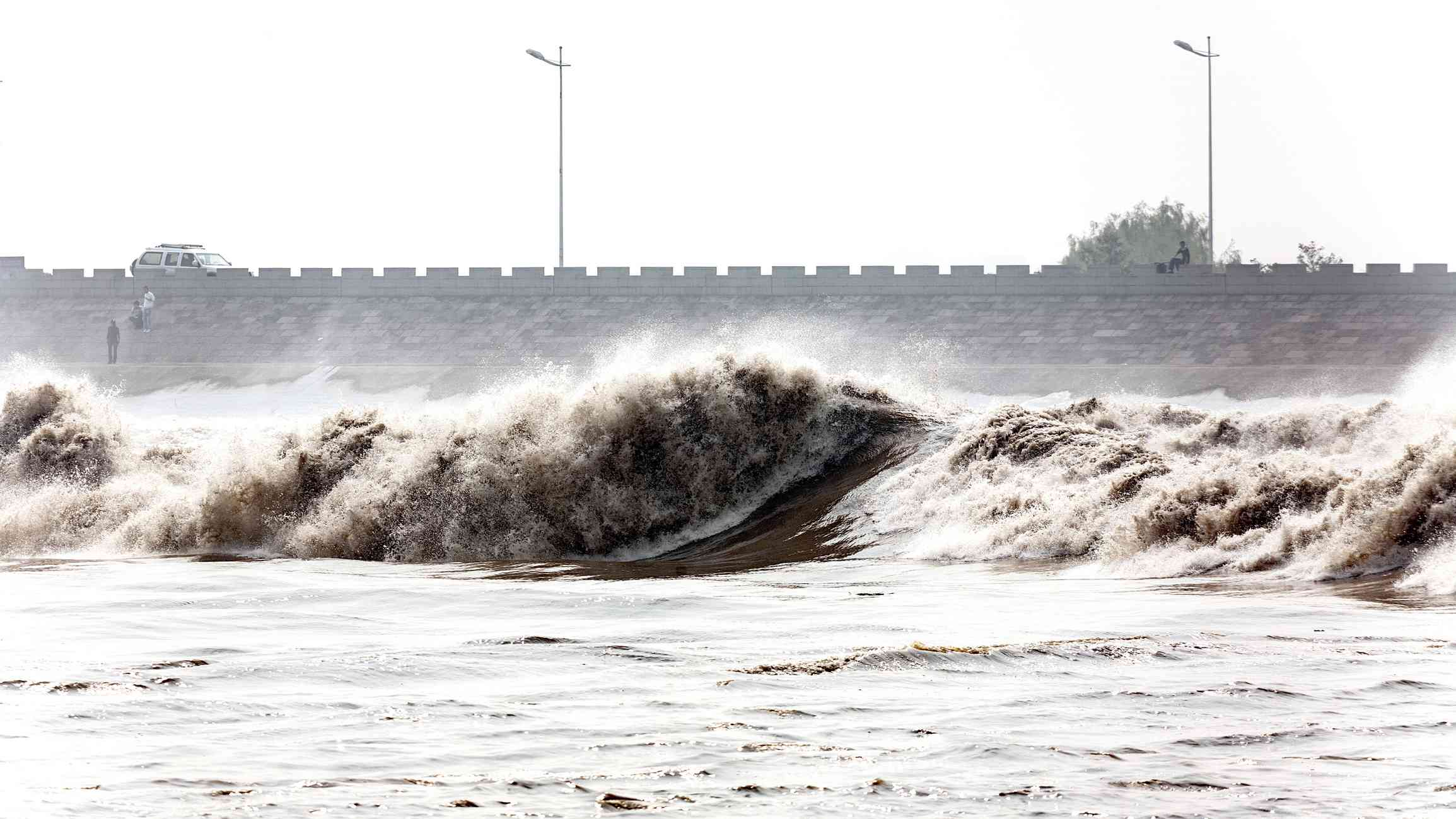 waves crashing during the Qiantang River tidal bore with a brick bridge in the distance under a foggy sky